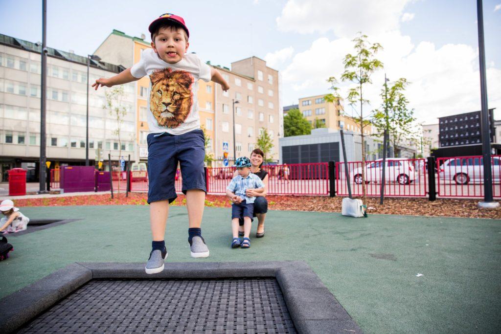 Poika hyppii trampoliinilla torin leikkipuistossa. Äiti on kyykyssä takana, odottaa vuoroa toisen pojan kanssa.