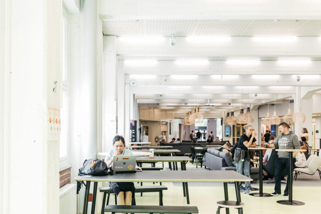 Opiskelija istuu tietokoneen ääressä isossa huoneessa, jossa taustalla monia opiskelijoita pöytien ääressä.