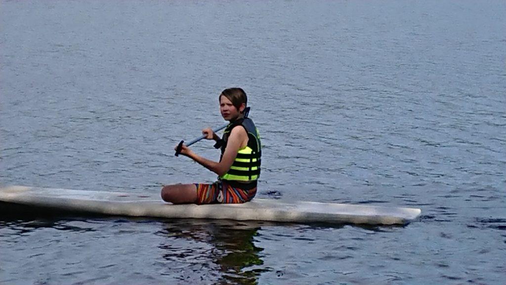 Koulupoika meloo sup-laudalla istuen järvessä. Hänellä on pelastusliivit päällään.
