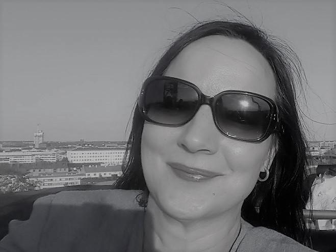 Mustavalkoinen kuva, Maija Väkeväinen aurinkolasit päässään, taustalla kaukana kaupunkimaisema.