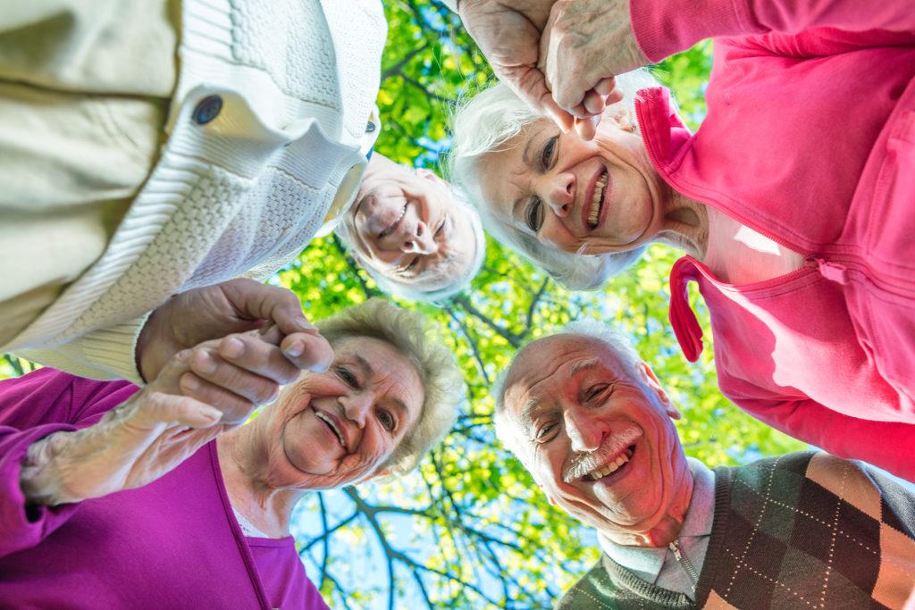 Kaksi eläkeikäistä naista ja miestä ringissä toisiaan kädestäpitäen, hymyilevät kasvot. Taustalla vihreälehtinen iso puu.