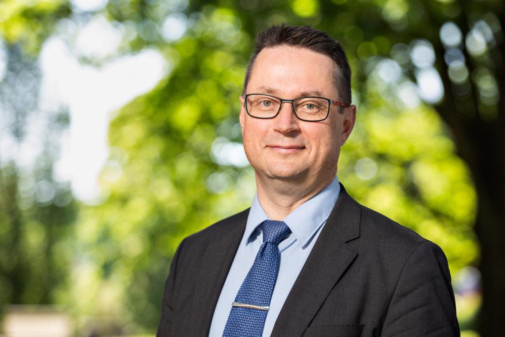 Tummahiuksinen keski-ikäinen mies seisoo puistossa. Hänellä on silmälasit sekä sininen paita ja ja harmaa puku yllään, kaulassa kravatti.