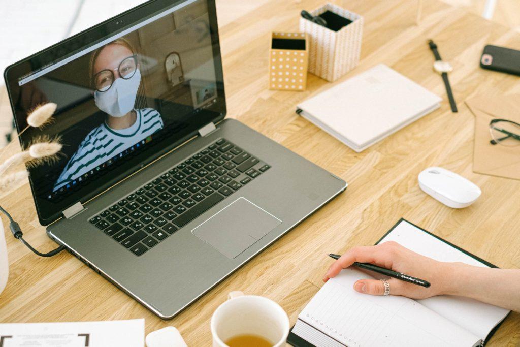Työpöydällä kannettava tietokone, jonka näytöllä nuori nainen. Hänellä kasvomaski kasvoillaan. Työpöydällä teekuppi, kalenteri, muistikirja, hiiri ja silmälasit. Kuvan alareunassa kalenterin päällä näkyy ihmisen oikea käsi, jossa kynä .