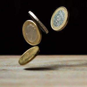 Pöydälle putoaa neljä euron kolikkoa. Musta tausta, ruskea puinen pöytä.