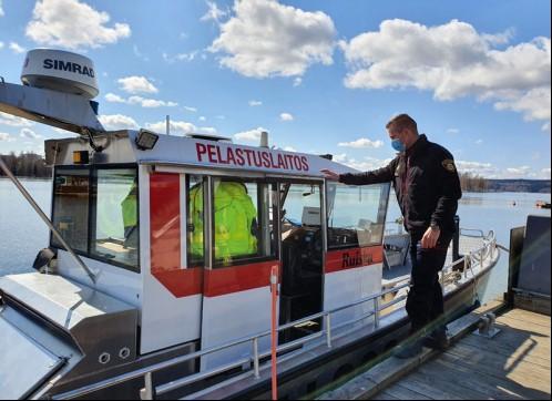 Pelastuslaitoksen vene laiturissa, henkilökuntaan kuuluva mies seisoo laiturilla veneen vieressä. Veneen sisällä näkyy useita pelastusliivejä.
