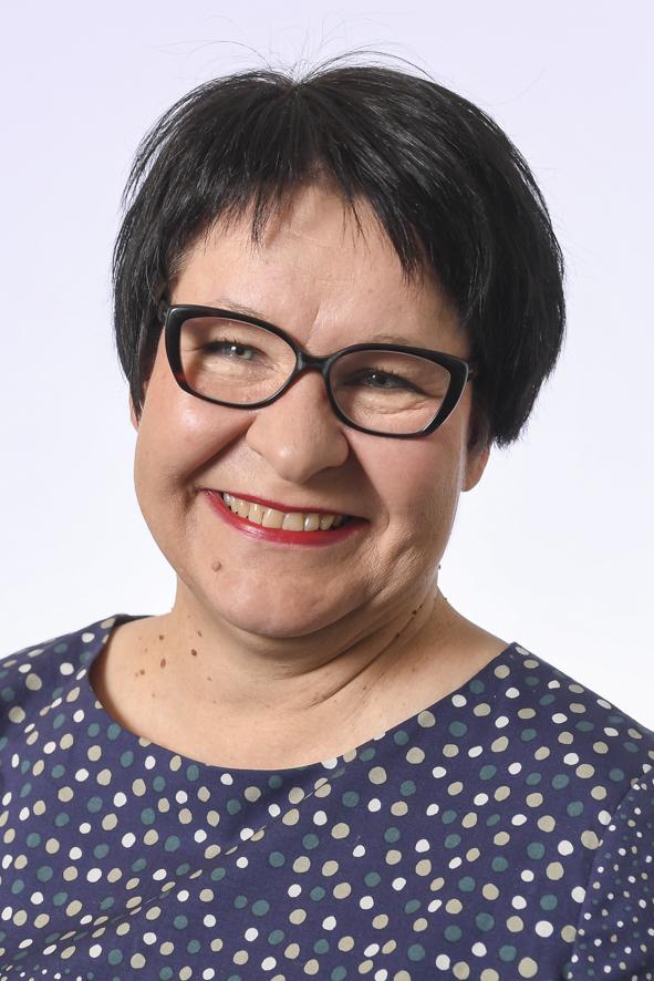 Hämeen vaalipiirin kansanedustaja, kasvokuva. Hymyilevä nainen, tummat, lyhyet hiukset ja tummatsankaiset silmälasit. Sininen paita jossa pieniä vihreitä, vaalean ruskeita ja valkoisia palloja.