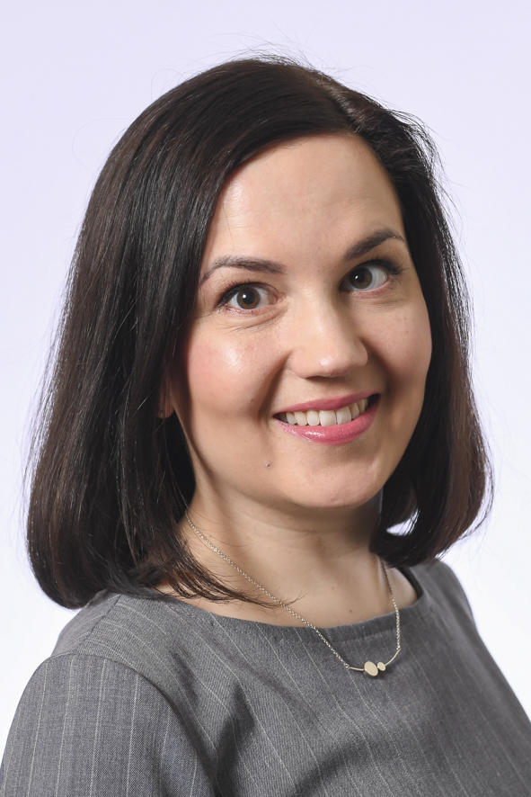 Hämeen vaalipiirin kansanedustaja, kasvokuva. Hymyilevä nainen, ruskeat hiukset. Harmaa liituraitainen mekko ja kaulaketju.