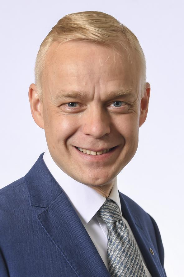 Hämeen vaalipiirin kansanedustaja Timo Heinonen. Kasvokuva. Vaaleahiuksinen mies, jolla yllään sininen pikkutakki, valkoinen paita ja siniharmaa solmio.