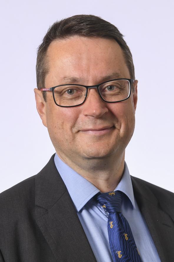 Päijät-Hämeen kansanedustaja Mika Kari. Kasvokuva. Hymyilevä ruskeahiuksinen mies, silmälasit. Yllään tumma puku, vaalean sininen paita ja Päijät-Hämeen liiton sininen solmio.