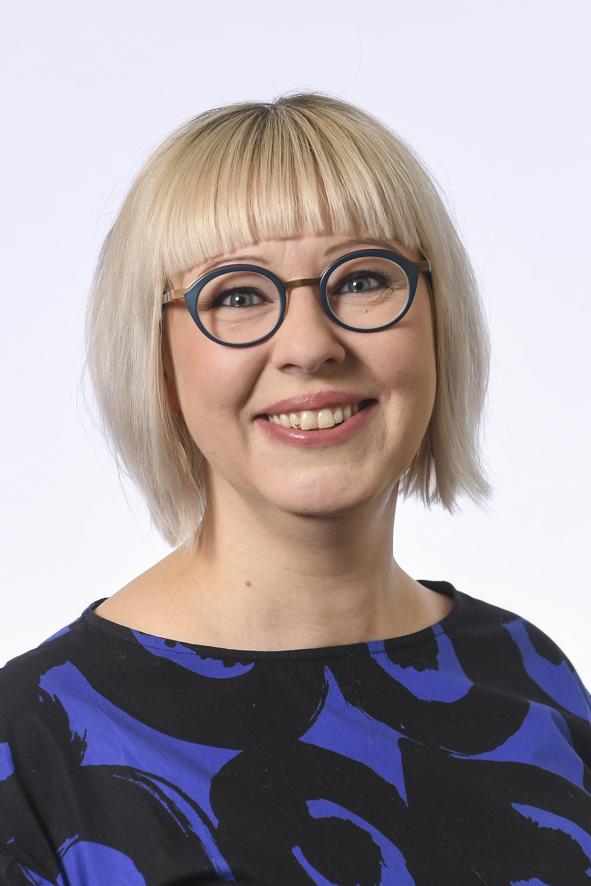 Hämeen vaalipiirin kansanedustaja, kasvokuva. Hymyilevä nainen, vaaleat, suorat hiukset. Sini-musta-kuvioinen paita. Isot pyöreät silmälasit.