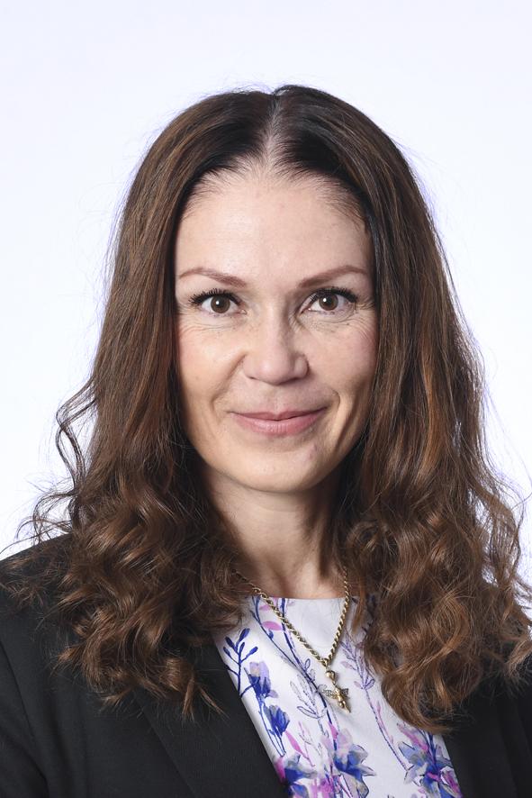 Hämeen vaalipiirin kansanedustaja, kasvokuva. Hymyilevä nainen, pitkät kiharat, ruskeat hiukset. Musta jakku, jonka alla vaalea kukkakuvioinen paita. Kaulassa kultariipus.