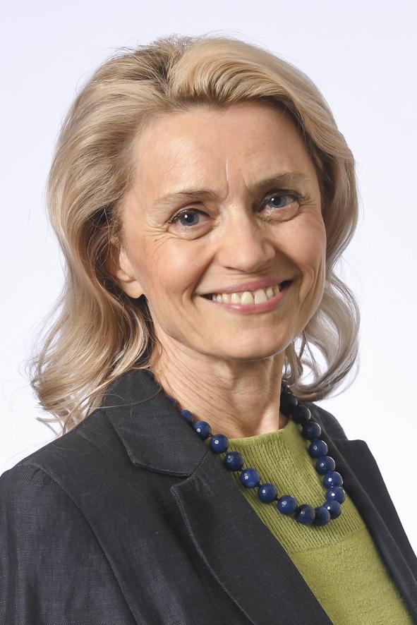 Hämeen vaalipiirin kansanedustaja, kasvokuva. Hymyilevä nainen, vaaleat pitkät hiukset. Yllään tumma jakku, jonka alla vihreä neulepaita. Kaulassa siniset helmet.