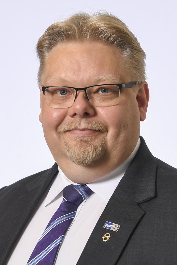 Päijät-Hämeen kansanedustaja Jari Ronkainen. Vaaleahiuksinen mies, jolla silmälasit, viikset ja parta. Tummanharmaa puku ja tummansinen solmio, jossa vaalean sinisiä vinoraitoja. Takin kauluksessa Perussuomalaiset-puolueen pinssi.