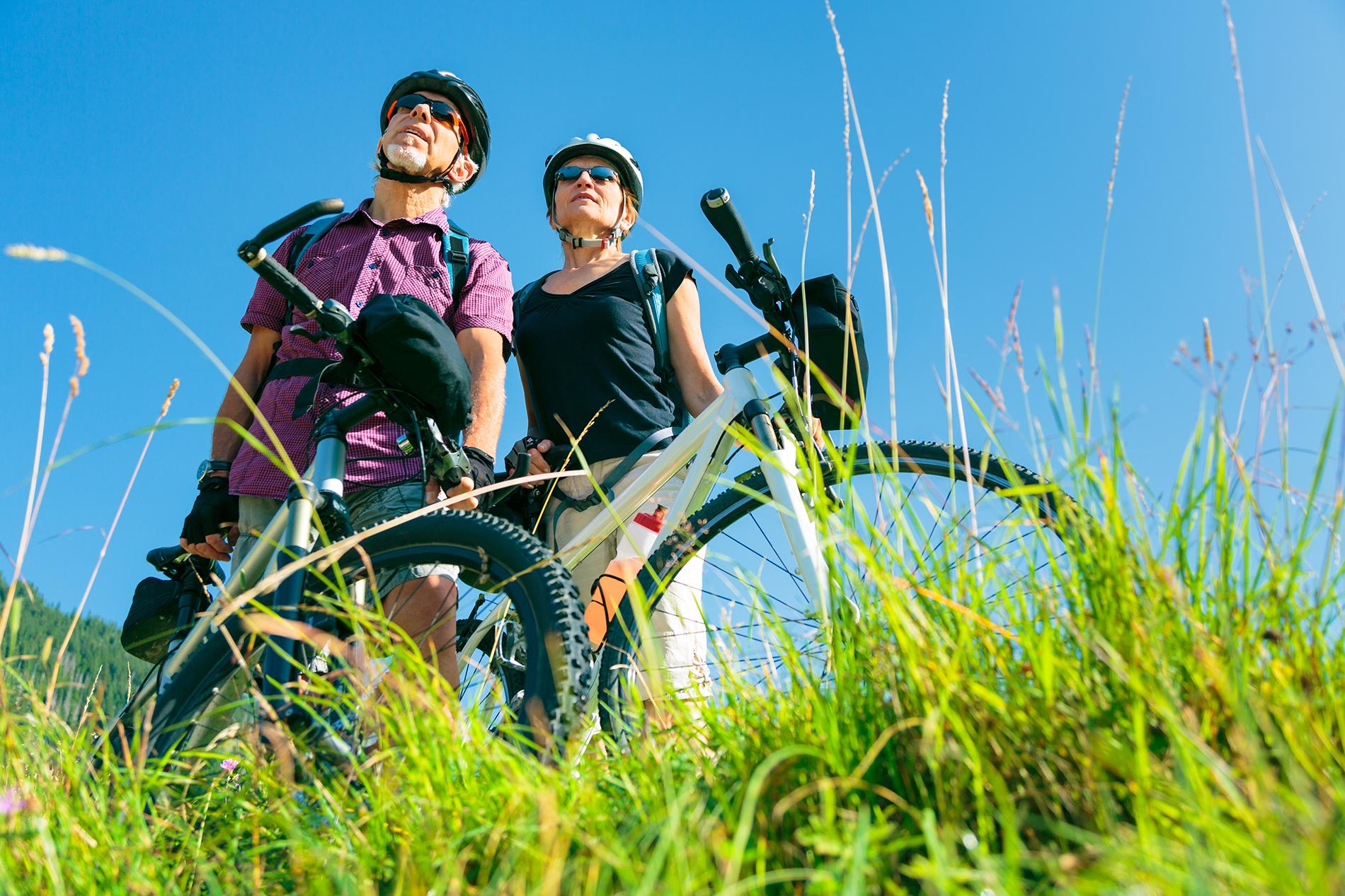 Pariskunta on pyörällä pysähtynyt niitylle ihailemaan maisemia.