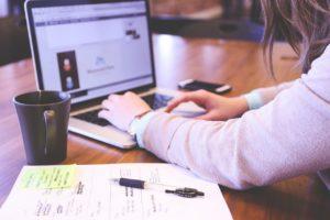 Miehen kädet työpöydällä, hän kirjoittaa kannettavalla tietokoneella. Pöydällä musta kahvikuppi ja paperiarkki, jonka päällä kynä.